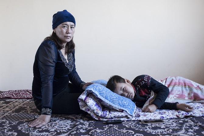 Turan Tilejbai mit ihrem Sohn Otanbek; ihr Mann wurde in China verhaftet, November 2018 / Foto © Konstantin Salomatin