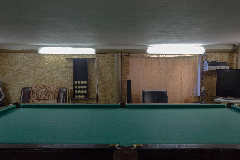 Raum mit Billardtisch in einer dreistöckigen Garage. Neben dem Stellplatz fürs Auto gibt es noch eine Banja, eine Küche und ein Schlafzimmer. Ein Zugang zum Dach ist in Planung/ Foto© Oksana Ozgur