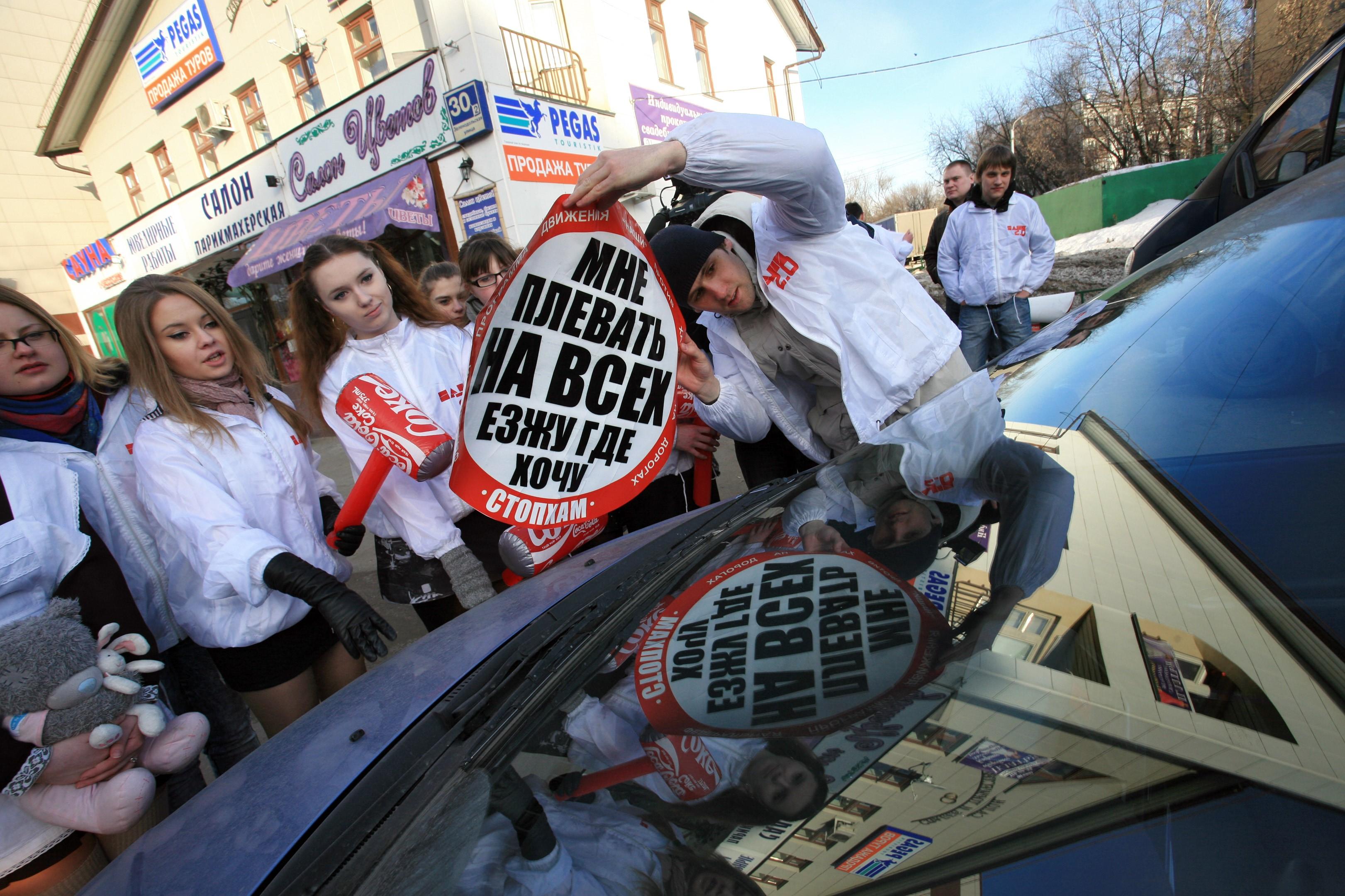 Foto © Ramil Gali / Kommersant. Aktion der Naschi-Bewegung im Rahmen der Kampagne StopCHAM gegen Autos, die z. B. über Gehwege fahren und dafür mit Aufklebern beklebt werden: Mir ist alles scheißegal, ich fahre wo ich will.