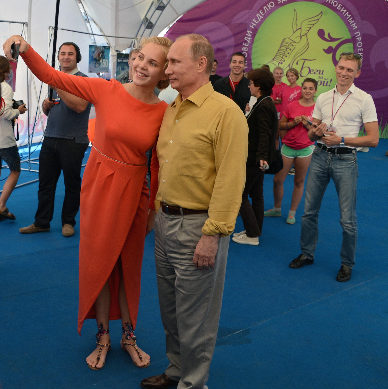 Foto © Dimitri Asarow / Kommersant. Präsident Wladimir Putin (Mitte) mit der Aktivistin des Projekts StopCHAM Oksana Mitrofanowa (links) während eines Treffens von Teilnehmern des Jugendforums Seliger 2013 im Gebiet Twer