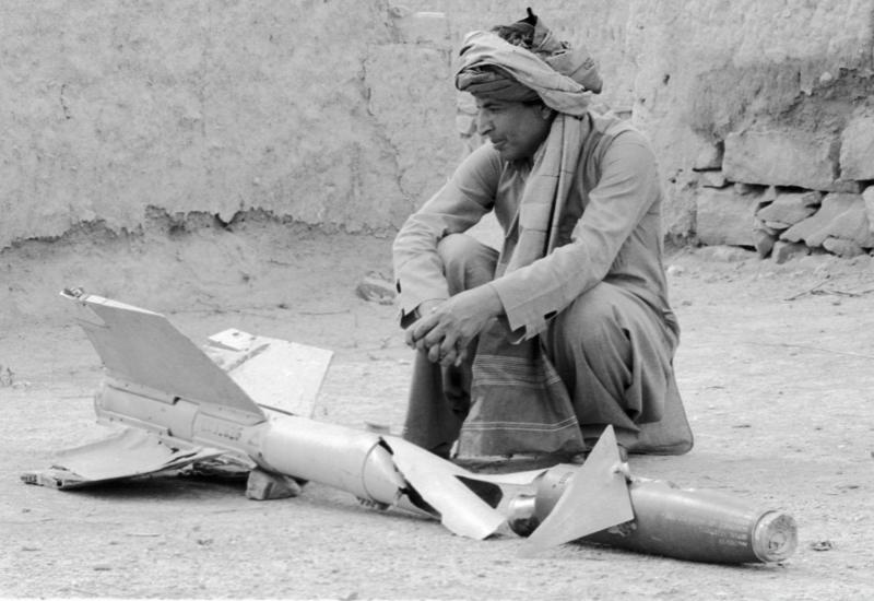 """Ein afghanischer Bauer hockt neben einer nicht explodierten US-amerikanischen """"Sidewinder""""-Rakete, 15.10.1987 / Foto © Alexander Graschenkow/Sputnik"""