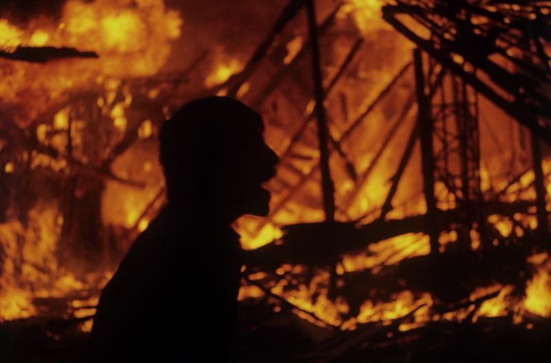 Ein Zivilist vor brennenden Wohnhäusern, Kabul, 06.03.1989 / Foto © Andrej Solomonow/Sputnik