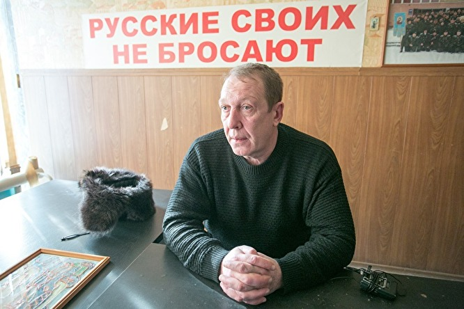 """Ataman Oleg Surnin, im Hintergrund ein Plakat mit der Aufschrift """"Russen lassen die eigenen Leute nicht im Stich"""""""